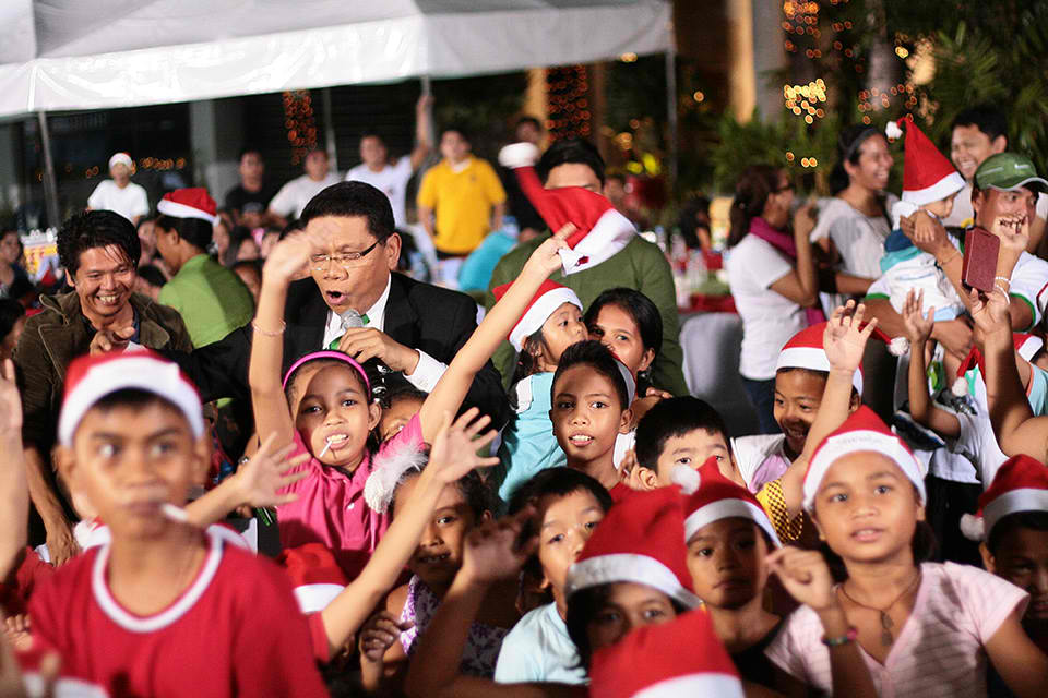 Mike Enriquez of 24 Oras, celebrating with children during Christmas