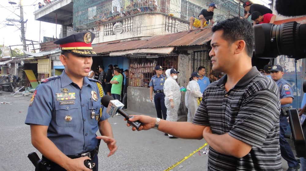 Veteran journalist Jiggy Manicad interviews a policeman.