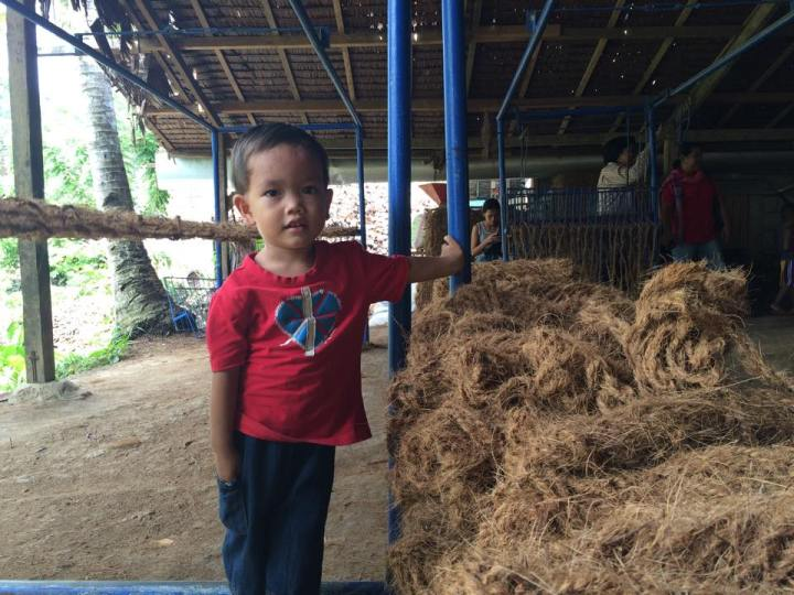 A child plays around the area where his parents mill coconut husks. (Photo by Lian Buan)