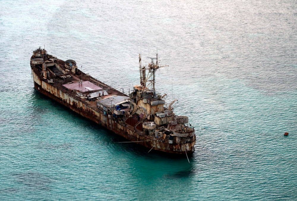 This areal photo taken through a glass window of a military plane shows the dilapidated BRP Sierra Madre ship of the Philippine Navy anchored near Ayungin Shoal with Filipino soldiers onboard to secure perimeter in the Spratly Islands in the South China Sea Modnay, May 11, 2015. Gen. Gregorio Pio Catapang, the Philippines' military chief, has flown to Pag-asa Island, a Filipino-occupied island in the South China Sea amid territorial disputes in the area with China, vowing to defend the islet and help the mayor develop tourism and marine resources there. (Ritchie B. Tongo/Pool Photo via AP)