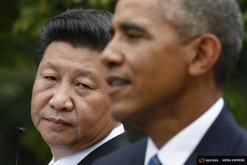 Chinese President Xi listens to U.S. President Obama during joint news conference in the Rose Garden of the White House in Washington