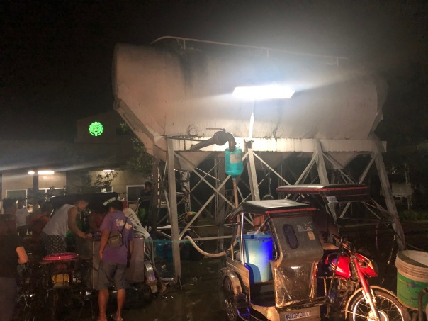 Antipolo residents line up well past midnight to seek water from a deep well. Large containers cost P40 each.