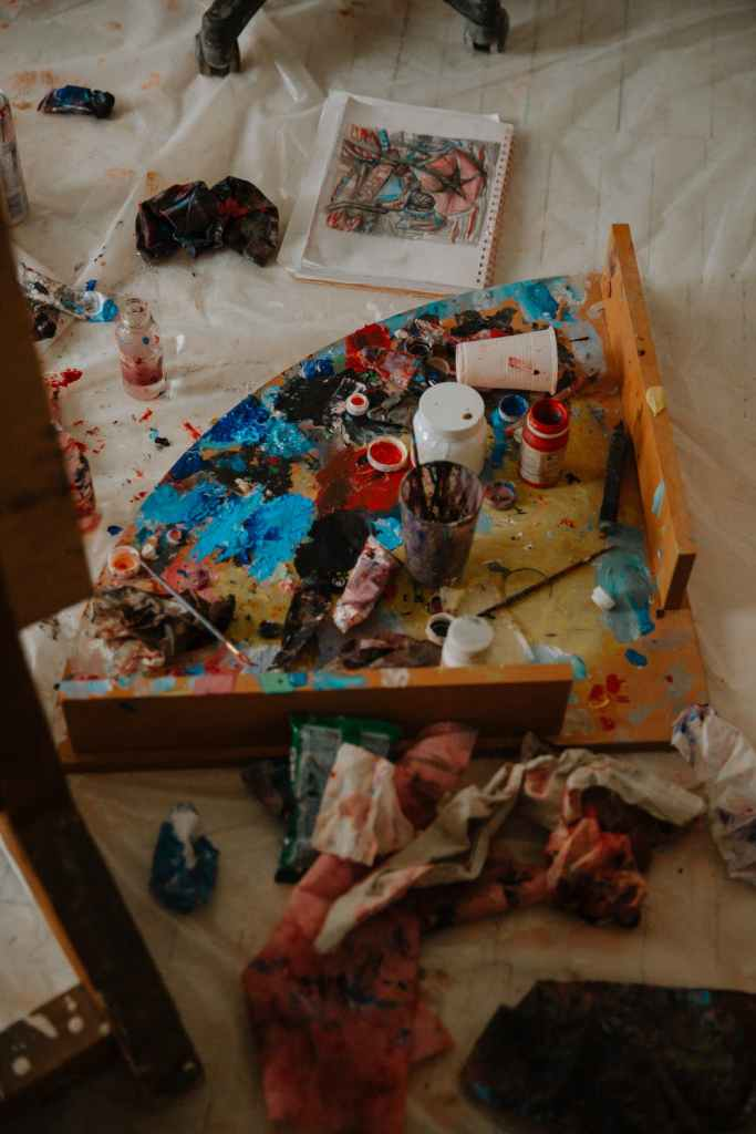From above of paints on palette near supplies placed on oilcloth in art studio